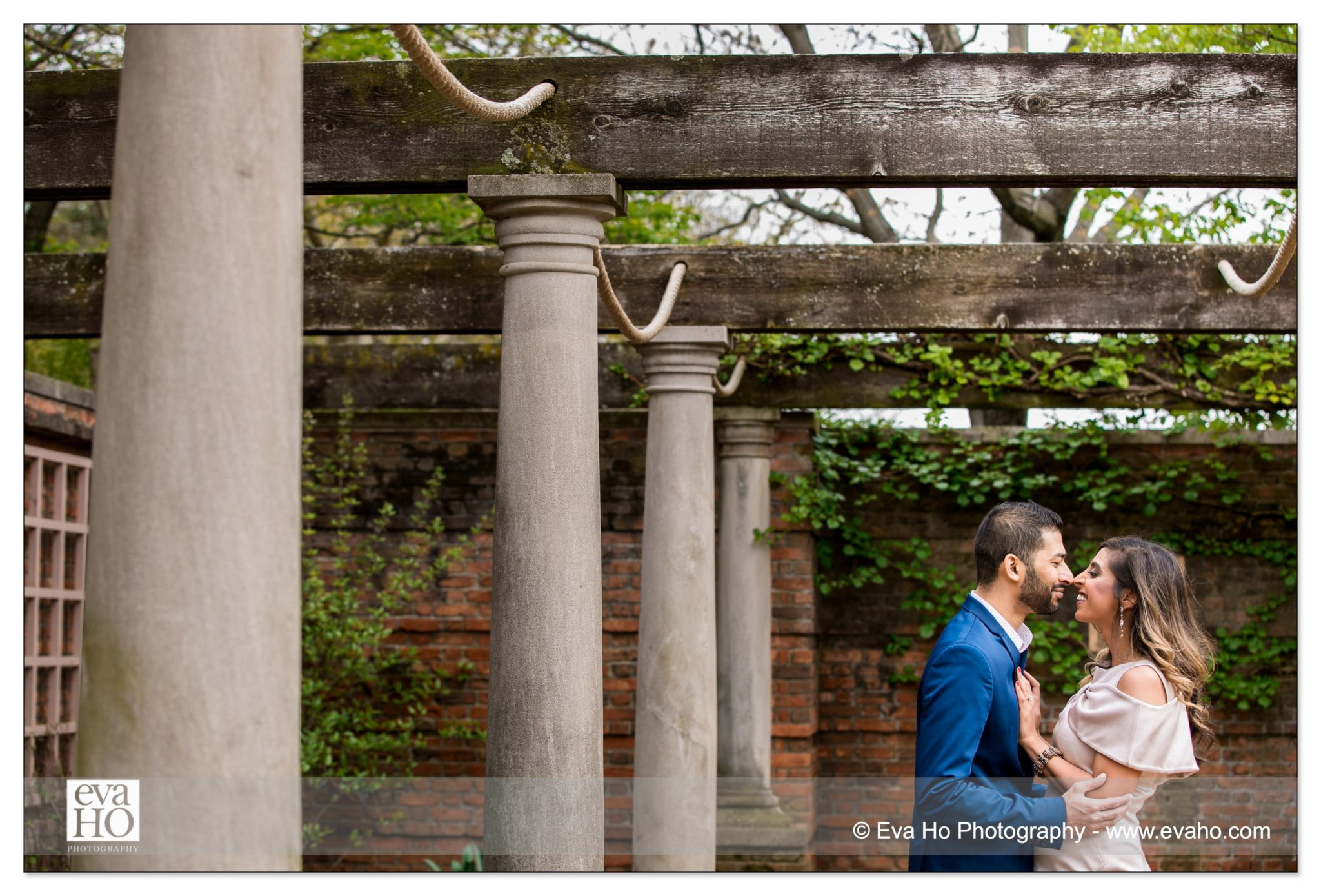 Couple snuggle under the beautiful Roman structure inside the Rose Garden at the Chicago Botanic Garden.